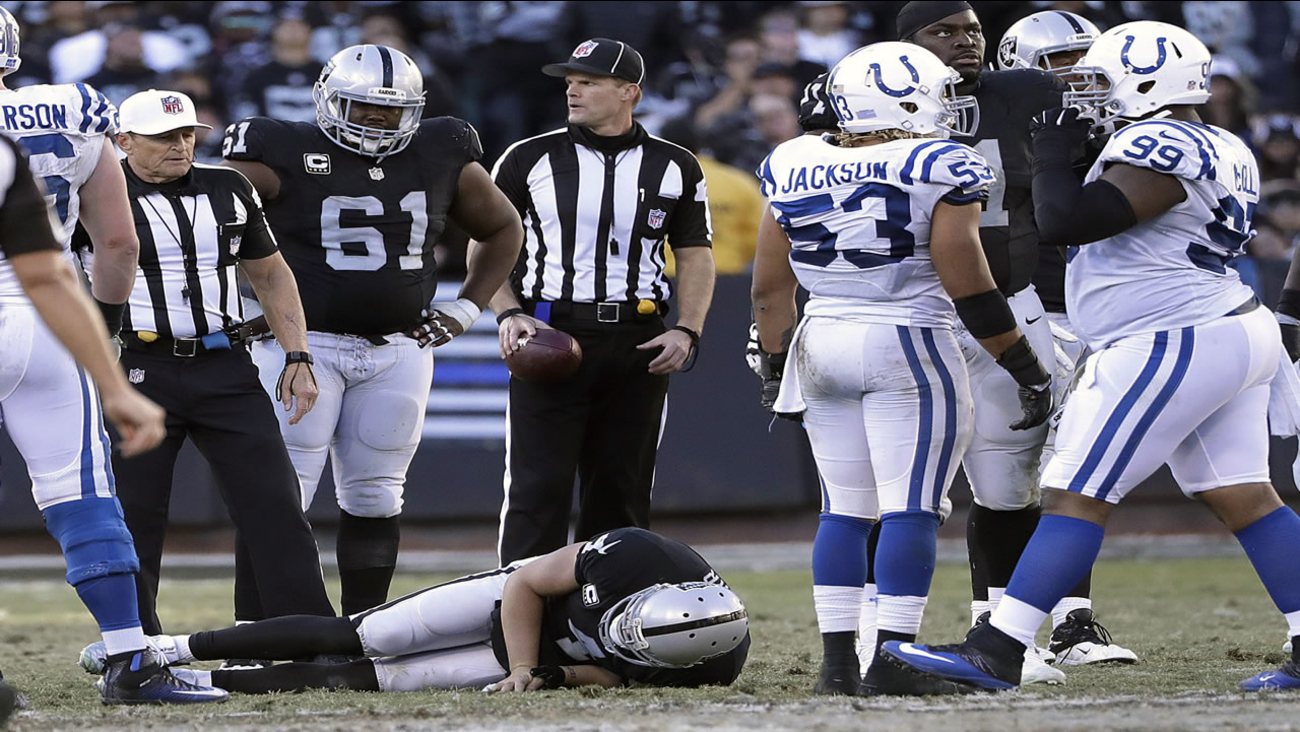 Oakland Raiders quarterback Derek Carr, bottom, remains on the field after being tackled by Indianapolis Colts inside linebacker Edwin Jackson on Dec. 24, 2016.