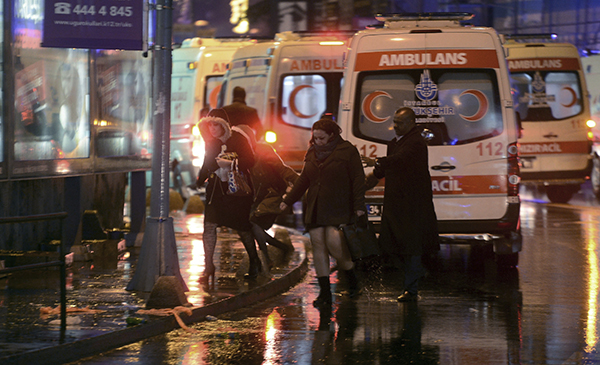 <div class='meta'><div class='origin-logo' data-origin='AP'></div><span class='caption-text' data-credit='IHA via AP'>People leave as medics and security officials work at the scene after an attack at a popular nightclub in Istanbul, early Sunday, Jan. 1, 2017.</span></div>