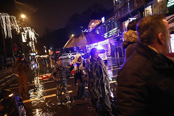 <div class='meta'><div class='origin-logo' data-origin='AP'></div><span class='caption-text' data-credit='IHA via AP'>People walk under rain near the scene of an attack in Istanbul, early Sunday, Jan. 1, 2017.</span></div>