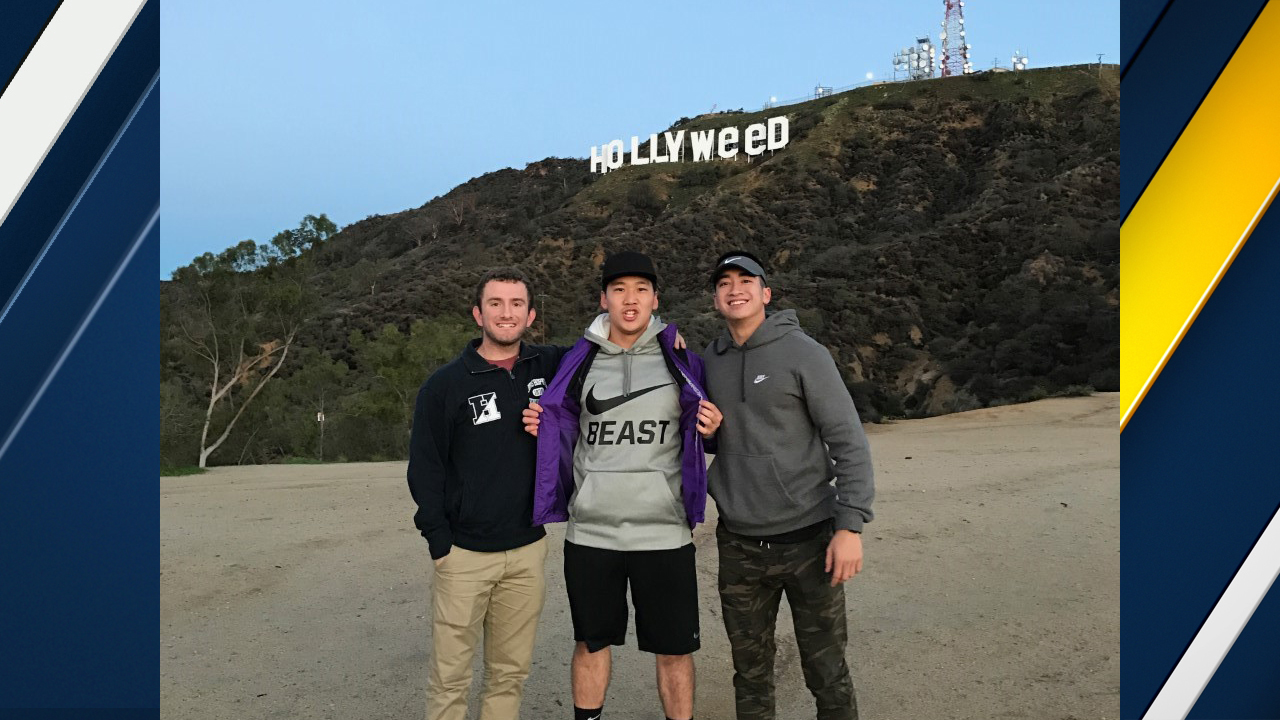 Alvin Kim and two fellow hikers pose in front the altered Hollywood sign on Sunday, Jan. 1, 2017.