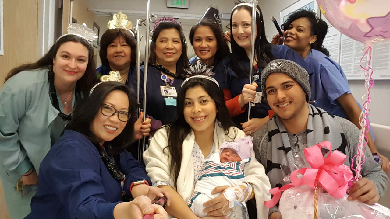 A family and hospital staff members are seen with a baby girl believed to be the first baby of 2017 to be born in the Bay Area.