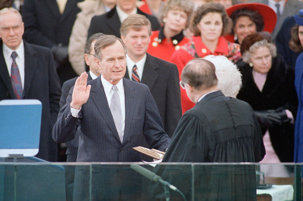 <div class='meta'><div class='origin-logo' data-origin='none'></div><span class='caption-text' data-credit='Ron Edmonds/AP Photo'>George H. W. Bush, left, raises his hand as he takes the oath of office as President of the United States outside the Capitol, Friday, Jan. 20, 1989, Washington, D.C.</span></div>