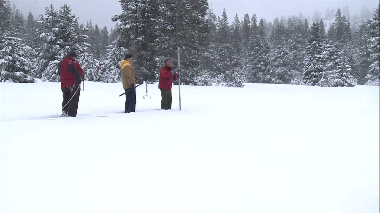 Surveyors plunge a pole into the Sierra Nevada to measure the snowpack in this undated file photo.