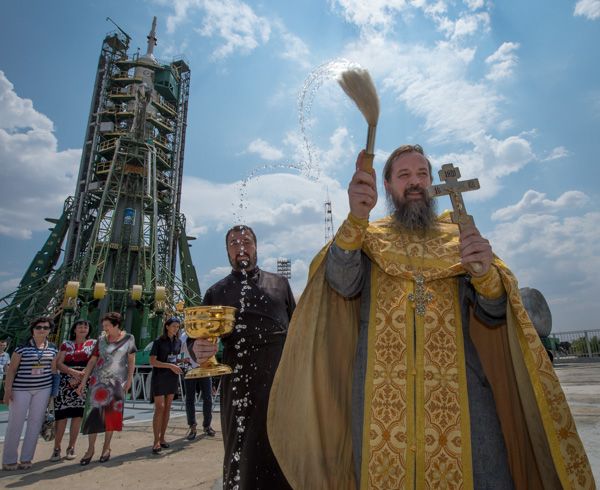 "<div class=""meta image-caption""><div class=""origin-logo origin-image none""><span>none</span></div><span class=""caption-text"">An Orthodox Priest blesses members of the media after he blessed the Soyuz rocket at the Baikonur Cosmodrome Launch pad on Wednesday, July 6, 2016 in Kazakhstan. (NASA/Bill Ingalls)</span></div>"