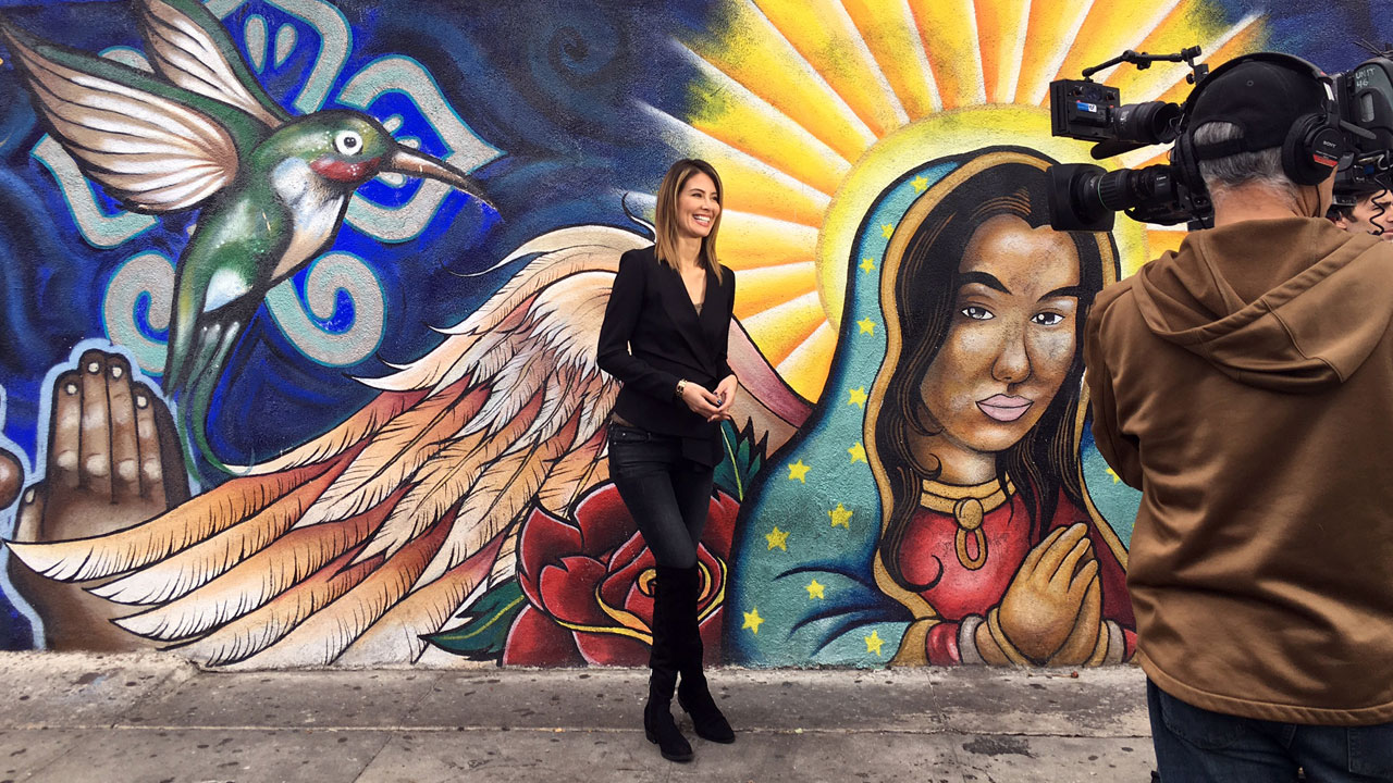 Vista L.A.'s Patricia Lopez is seen near a mural depicting the Virgin of Guadalupe.