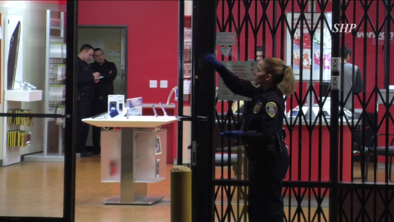 Authorities combed a Verizon Wireless store for evidence after suspects stole iPhones and cash at the Manhattan Beach location on Tuesday, Jan. 3, 2016.