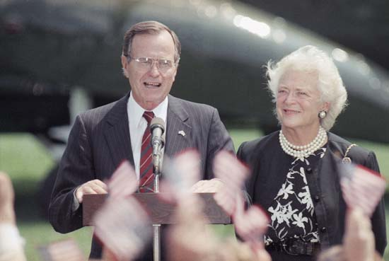 <div class='meta'><div class='origin-logo' data-origin='none'></div><span class='caption-text' data-credit='AP'>President George H.W. Bush, left, and first lady Barbara Bush smile as well-wishers wave U.S. flags upon their arrival on the south lawn of the White House in DC July 18, 1989.</span></div>
