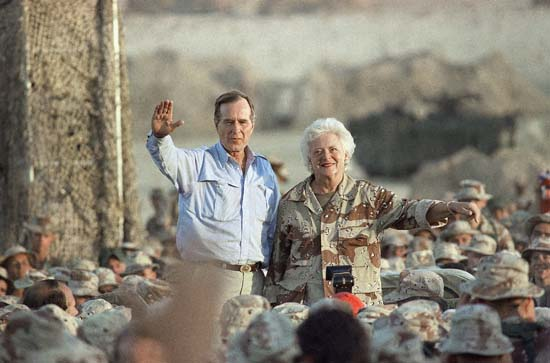 <div class='meta'><div class='origin-logo' data-origin='none'></div><span class='caption-text' data-credit='ASSOCIATED PRESS'>Pres. George H. W. Bush, left, and First Lady Barbara Bush wave to U.S Marines at the desert encampment during a Thanksgiving visit, Thursday, Nov. 22, 1990, Saudi Arabia.</span></div>