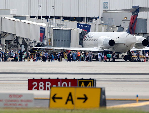 <div class='meta'><div class='origin-logo' data-origin='none'></div><span class='caption-text' data-credit='Lynne Sladky/AP Photo'>People stand on the tarmac at the Fort Lauderdale-Hollywood International Airport after a shooter opened fire inside the terminal.</span></div>