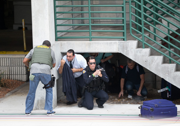 "<div class=""meta image-caption""><div class=""origin-logo origin-image none""><span>none</span></div><span class=""caption-text"">Law enforcement personnel shield civilians outside a garage area at Fort Lauderdale-Hollywood International Airport, after a shooter opened fire inside a terminal. (Wilfredo Lee/AP)</span></div>"