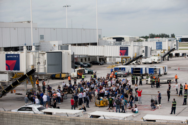 <div class='meta'><div class='origin-logo' data-origin='none'></div><span class='caption-text' data-credit='Wilfredo Lee/AP'>People stand on the tarmac at the Fort Lauderdale-Hollywood International Airport after a shooter opened fire inside a terminal of the airport.</span></div>