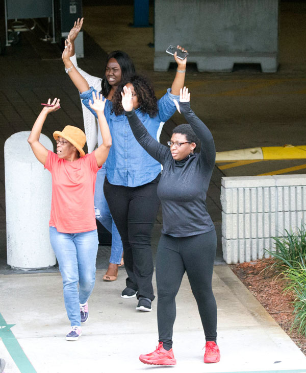 <div class='meta'><div class='origin-logo' data-origin='none'></div><span class='caption-text' data-credit='Wilfredo Lee/AP Photo'>People leave a garage area with their hands up in the air outside Fort Lauderdale-Hollywood International Airport, Friday, Jan. 6, 2017.</span></div>