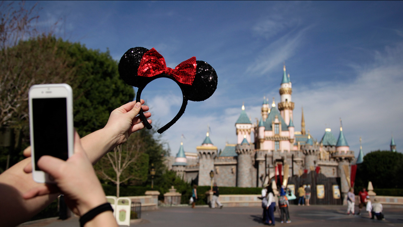 In this file photo, a guest takes pictures of her hairband with the Sleeping Beauty's Castle in the background at Disneyland.