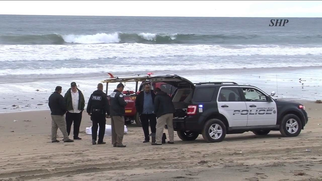 Law enforcement officials are seen in Hermosa Beach, where a woman's body washed ashore on Friday, Jan. 13, 2107.