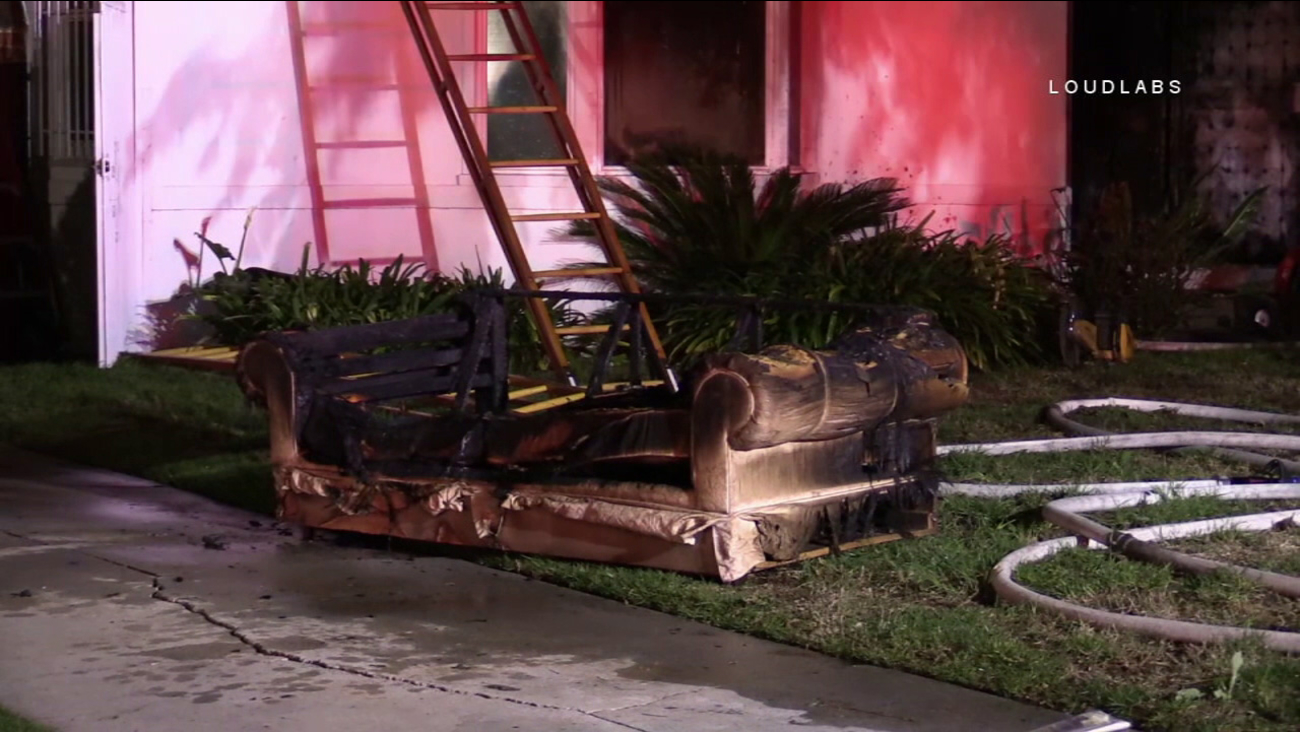 A charred sofa is seen in front of home in South Los Angeles after a fatal fire on Sunday, Jan. 15, 2017.