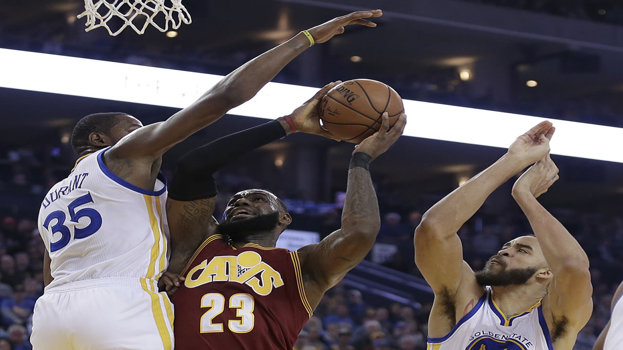 Cleveland Cavaliers' LeBron James, center, shoots between Golden State Warriors' Kevin Durant (35) and JaVale McGee, right in Oakland, Calif. on Jan. 16, 2017.