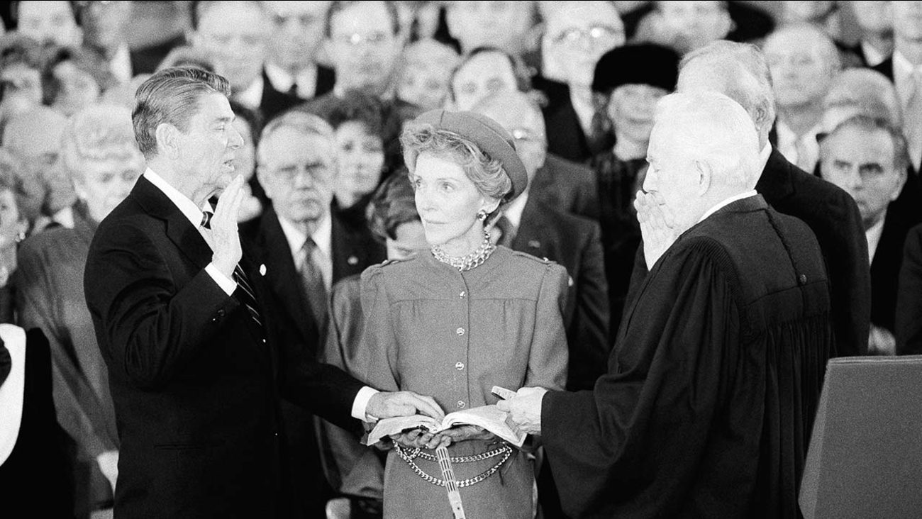 FILE: President Ronald Reagan repeats the oath of office of the President as his wife Nancy Reagan holds the Bible during the ceremony under the Rotunda of the Capitol