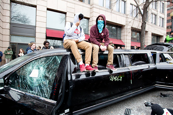 "<div class=""meta image-caption""><div class=""origin-logo origin-image none""><span>none</span></div><span class=""caption-text"">Demonstrators sit at the top of a limousine with the windows broken during the demonstration in downtown Washington Friday, Jan. 20, 2017. (Jose Luis Magana/AP Photo)</span></div>"