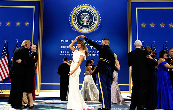"<div class=""meta image-caption""><div class=""origin-logo origin-image none""><span>none</span></div><span class=""caption-text"">President Donald Trump dances with Navy Petty Officer 2nd Class Catherine Cartmell as first lady Melania Trump is spun by Army Staff Sgt. Jose A. Medina at a ball on Jan. 21, 2017. (Alex Brandon/AP Photo)</span></div>"