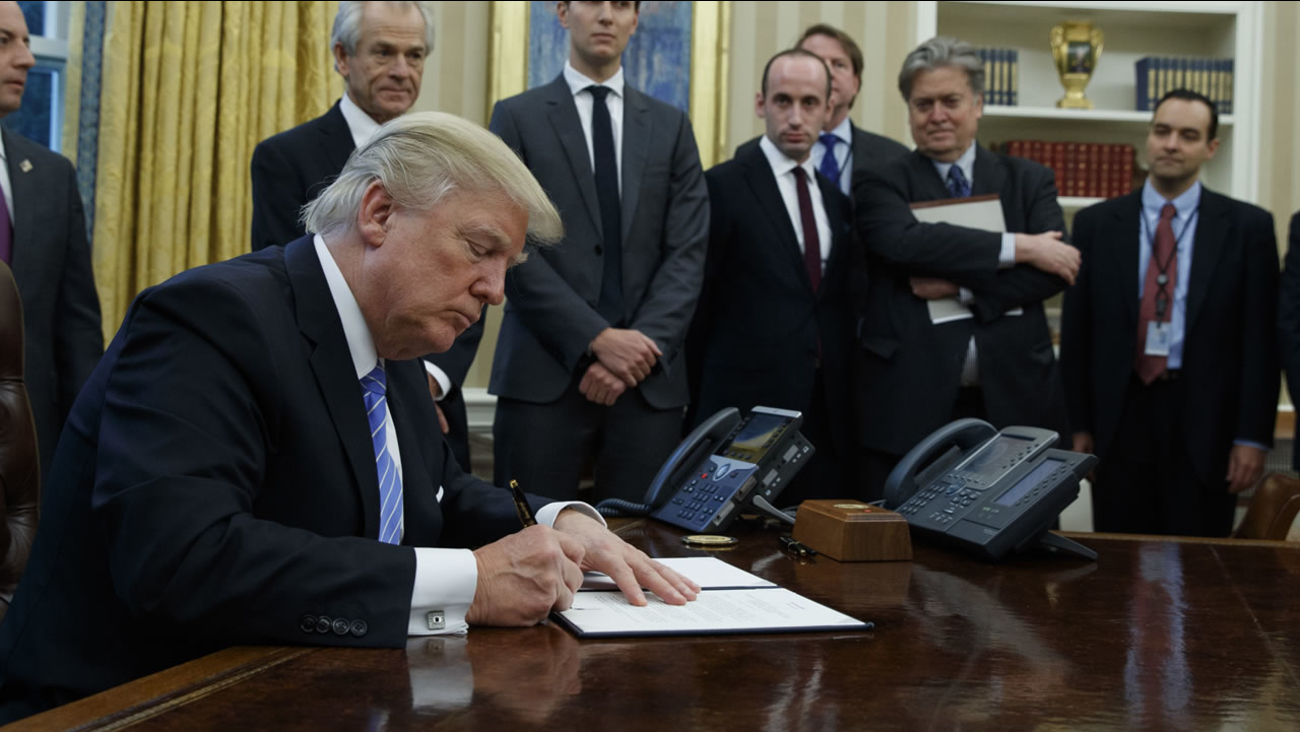 President Donald Trump signs an executive order implementing a federal government hiring freeze, Monday, Jan. 23, 2017.