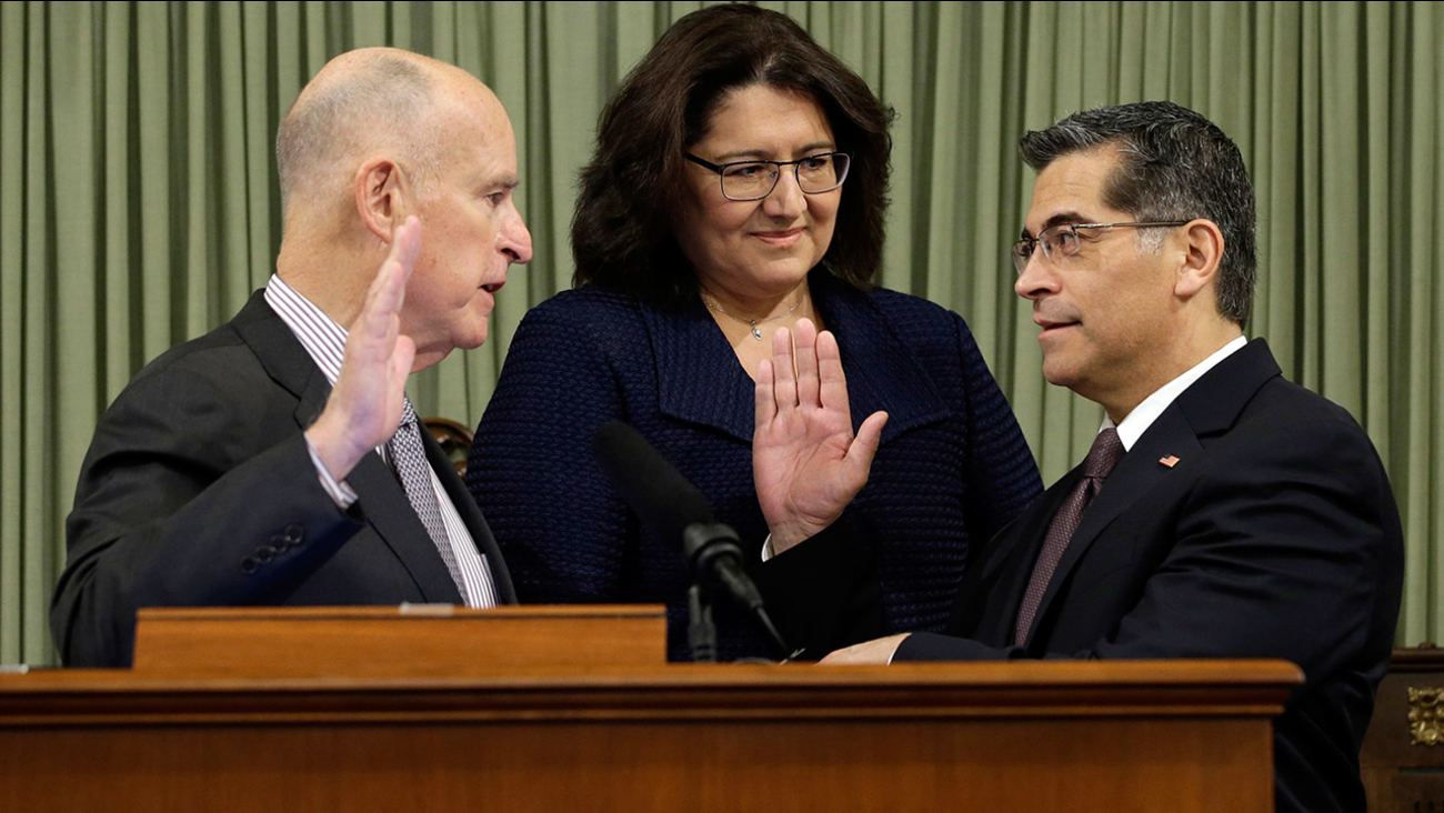 Xavier Becerra, right, is sworn in as California Attorney General by Gov. Jerry Brown, left, as Becerra's wife, Dr. Carolina Reyes looks on Tuesday, Jan. 24, 2017.