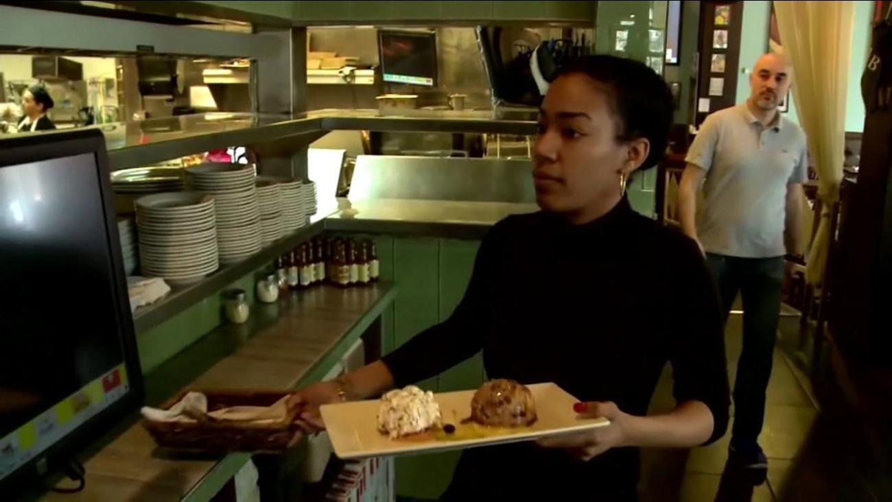 A waitress carries desserts at a restaurant.