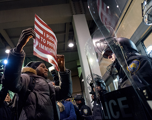 <div class='meta'><div class='origin-logo' data-origin='AP'></div><span class='caption-text' data-credit='AP Photo/Craig Ruttle'>A protester stands facing police officers at an entrance of Terminal 4 at John F. Kennedy International Airport in New York, Saturday, Jan. 28, 2017.</span></div>