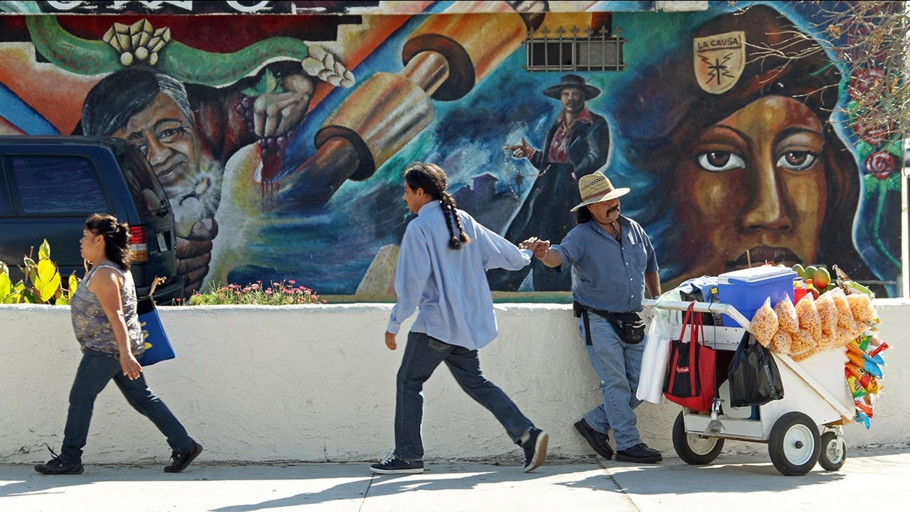 A street vendor greets an acquaintance in front the Maravilla Meat Market, with a mural depicting Cesar Chavez, left, in East Los Angeles, on Wednesday, Feb. 8, 2012.