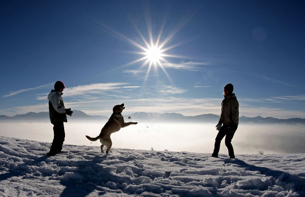 <div class='meta'><div class='origin-logo' data-origin='none'></div><span class='caption-text' data-credit='(AP Photo/Uwe Lein)'>Strollers play with a dog in the snow on a sunny winter day near Irschenberg, southern Germany on Saturday, Dec. 22, 2007.</span></div>