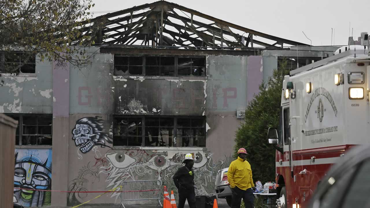A pair of Oakland fire officials walk past the remains of the Ghost Ship warehouse fire Wednesday, Dec. 7, 2016, in Oakland, Calif.