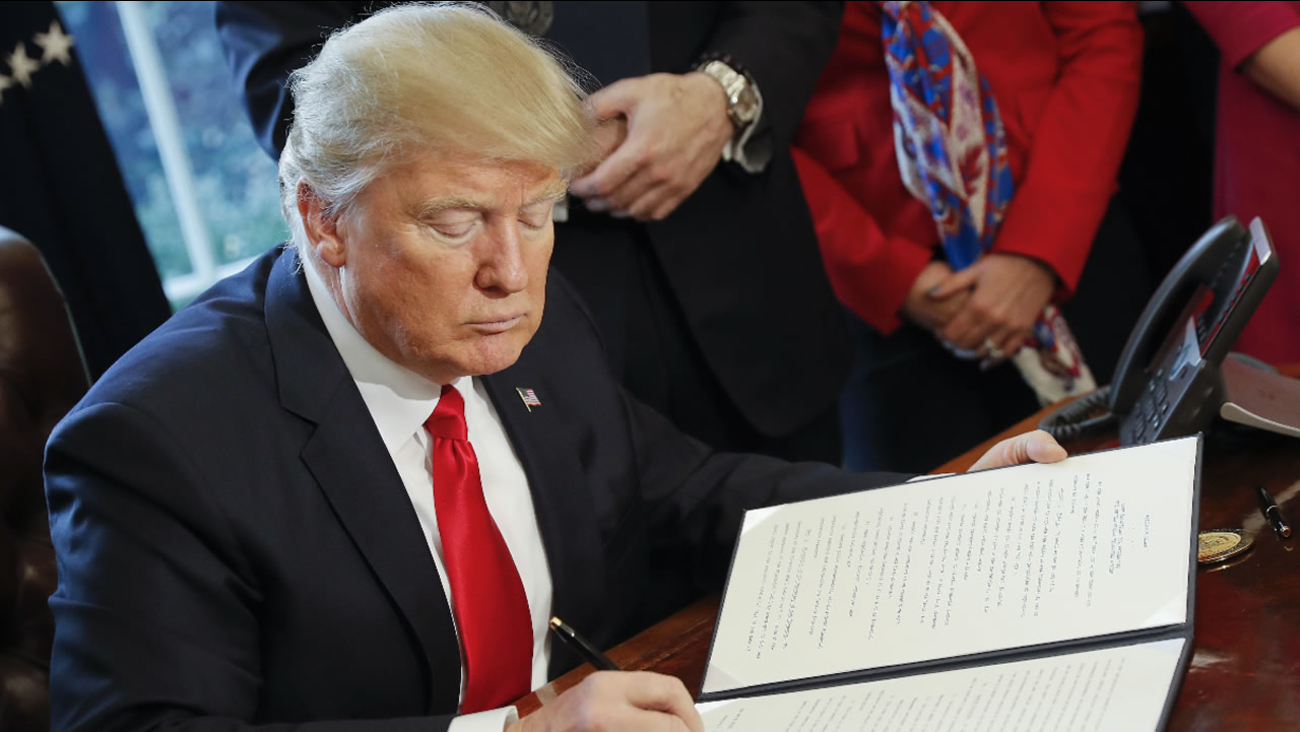 President Donald Trump signs an executive order in the Oval Office of the White House in Washington, Friday, Feb. 3, 2017.