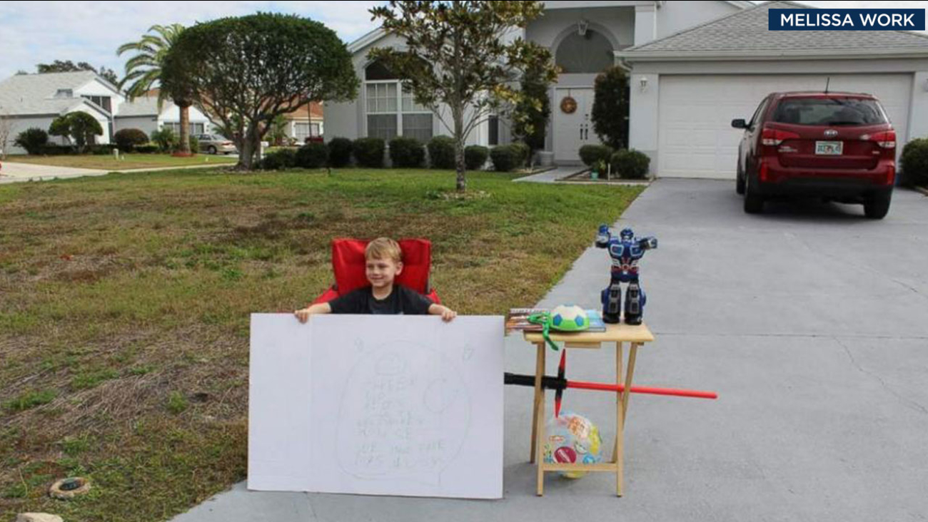 """Blake Work, 6, is shown holding his sign in front of his """"free toy"""" stand at his Florida home."""