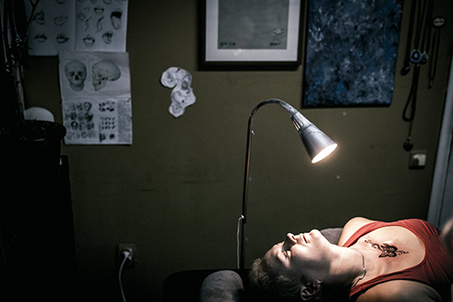 "<div class=""meta image-caption""><div class=""origin-logo origin-image ap""><span>AP</span></div><span class=""caption-text"">A woman lies on the bed at a tattoo artist's to get a tattoo done to conceal a scar from a domestic violence attack in Ufa, Russia. (AP Photo/Vadim Braydov)</span></div>"