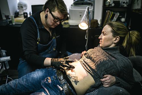 "<div class=""meta image-caption""><div class=""origin-logo origin-image ap""><span>AP</span></div><span class=""caption-text"">Yevgeniya Zakhar gives a tattoo to Nadezhda, a victim of domestic violence. (AP Photo/Vadim Braydov)</span></div>"