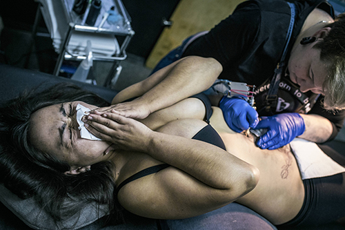 "<div class=""meta image-caption""><div class=""origin-logo origin-image ap""><span>AP</span></div><span class=""caption-text"">Guldar, a victim of domestic violence, left, cringes from pain as artist Yevgeniya Zakhar works on her tattoo in Ufa, Russia. (AP Photo/Vadim Braydov)</span></div>"