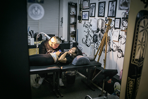 "<div class=""meta image-caption""><div class=""origin-logo origin-image ap""><span>AP</span></div><span class=""caption-text"">Tattoo artist Yevgeniya Zakhar works with a client, a victim of domestic violence, in Ufa, Russia. (AP Photo/Vadim Braydov)</span></div>"