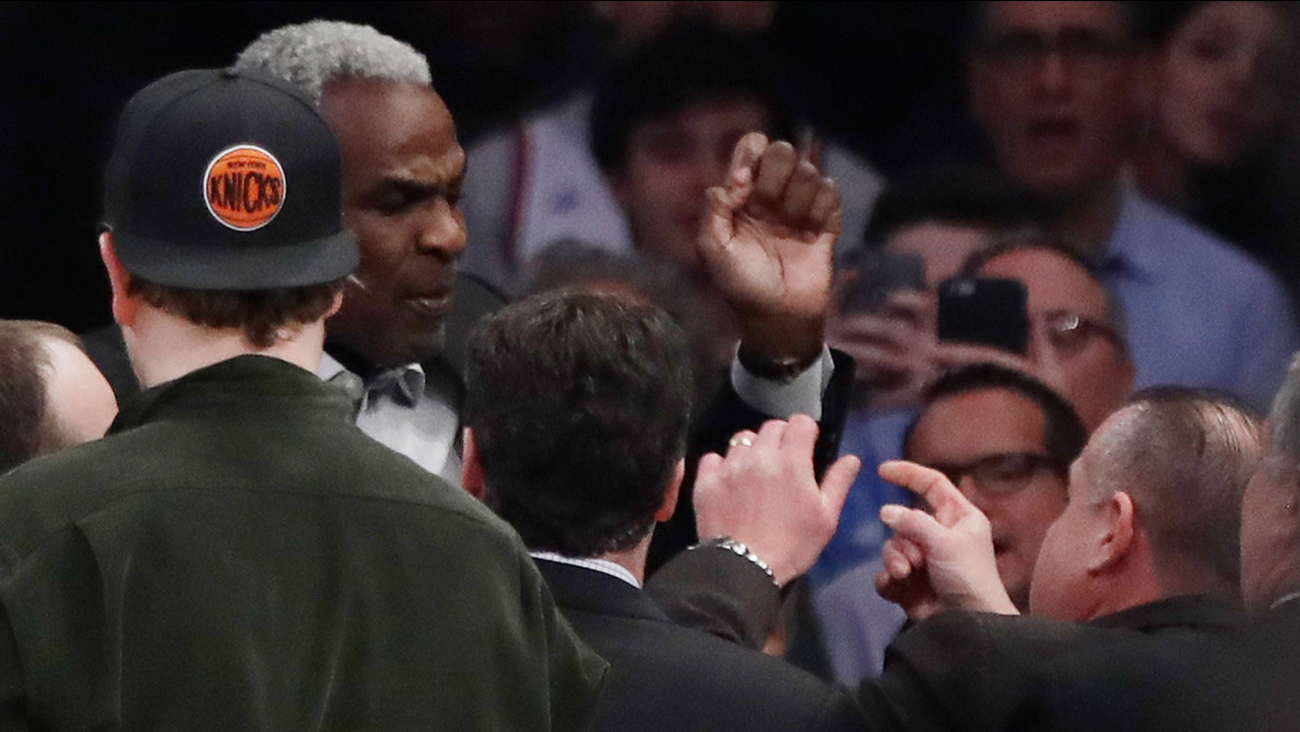Former New York Knicks player Charles Oakley exchanges words with a security guard during the first half of an NBA basketball game on Wednesday, Feb. 8, 2017.
