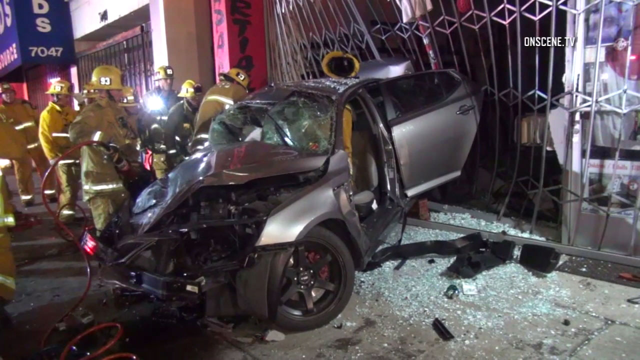 Firefighters aid victims in a deadly crash in Reseda on Saturday, Feb. 11, 2017.