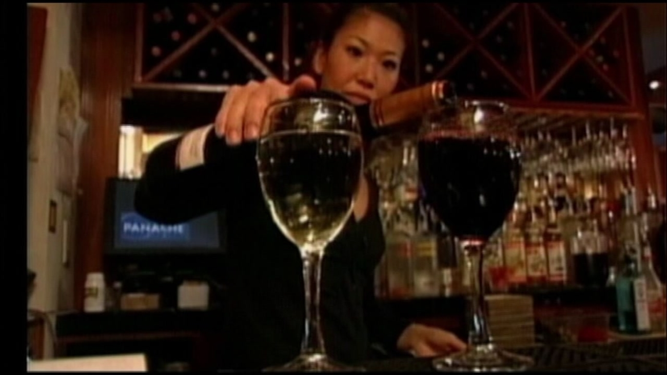 This is an undated image of a woman pouring a glass of wine.