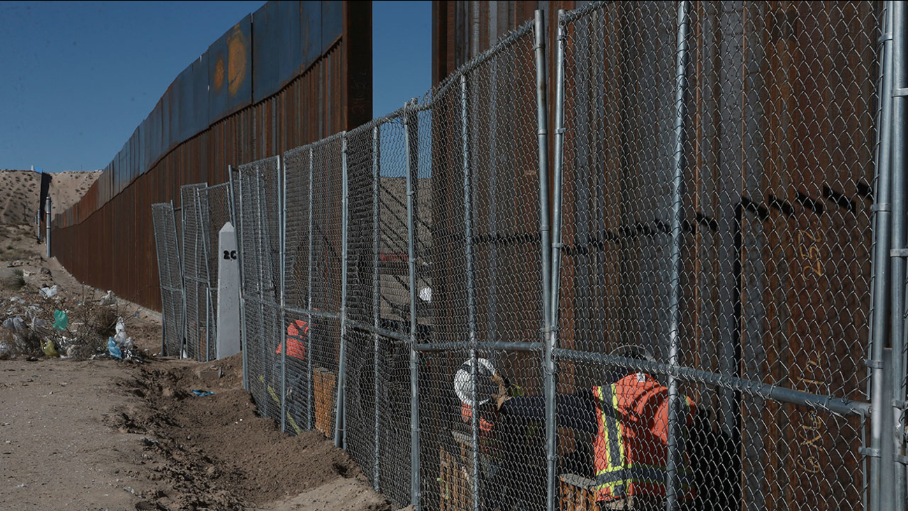 Workers raise a taller fence along the New Mexico-Mexico border on Jan. 25, 2017.