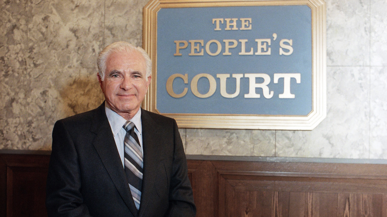 "Joseph Wapner, star of ""The People's Court,"" is seen in front of the television show's signature logo on Oct. 22, 1986."