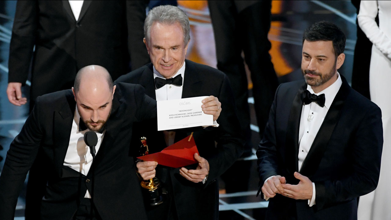 'La La Land' producer Jordan Horowitz holds up the winner card reading actual Best Picture winner 'Moonlight' with actor Warren Beatty and host Jimmy Kimmel onstage.