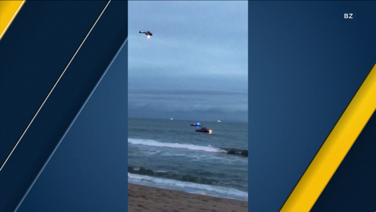A bystander's video shows a Coast Guard helicopter and boats searching for a missing swimmer off Bolsa Chica State Beach.