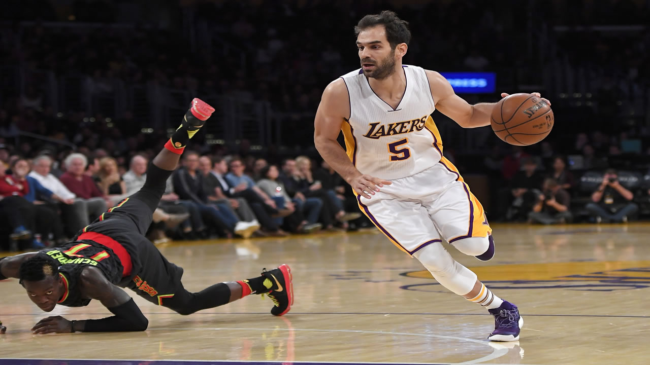 Los Angeles Lakers guard Jose Calderon, right, of Spain, drives toward the basket as Atlanta Hawks guard Dennis Schroder, of Germany, falls during an NBA game.