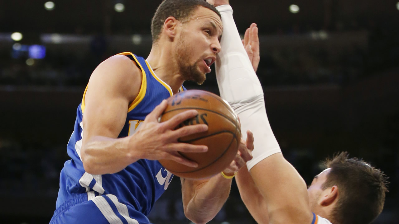 Warriors' Stephen Curry bumps into Knicks' Willy Hernangomez as he goes up for a layup in a game at Madison Square Garden in New York on March 5, 2017. (AP Photo/Kathy Willens)