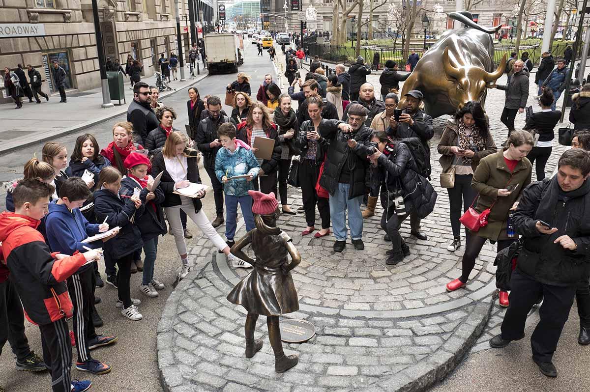 <div class='meta'><div class='origin-logo' data-origin='AP'></div><span class='caption-text' data-credit='AP Photo/Mark Lennihan'>A crowd gathers around a statue of a fearless girl facing the Wall Street Bull, Wednesday, March 8, 2017, in New York.</span></div>