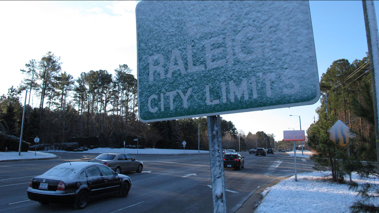 Wind-blown snow nearly obscures a city limits sign in Raleigh