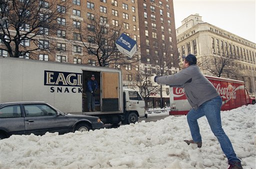 <div class='meta'><div class='origin-logo' data-origin='AP'></div><span class='caption-text' data-credit='AP'>A truck driver tosses a box over a mound of ice and snow to a waiting helper as he makes deliveries in New York Monday morning, March 15, 1993.</span></div>