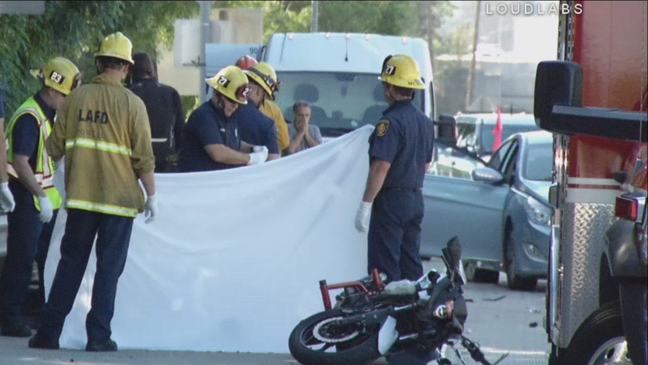 Firefighters and witnesses stand near the body of a deceased motorcyclist after a crash on the northbound 405 Freeway on Sunday, March 12, 2017.