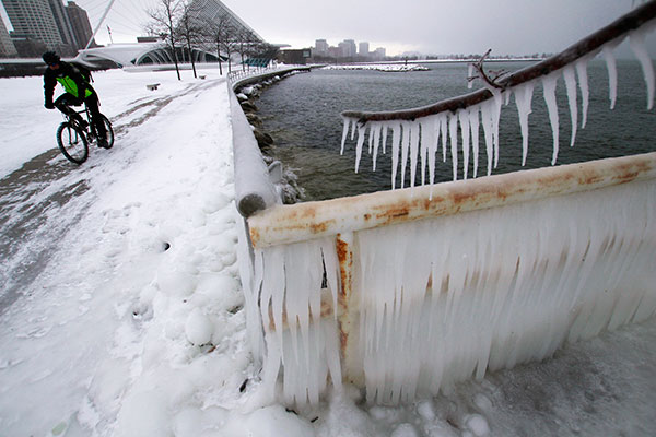 """<div class=""""meta image-caption""""><div class=""""origin-logo origin-image none""""><span>none</span></div><span class=""""caption-text"""">A man pedals his bike past some ice along Lake Michigan in downtown Milwaukee on Tuesday, March 14, 2017. (Carrie Antlfinger/AP Photo)</span></div>"""